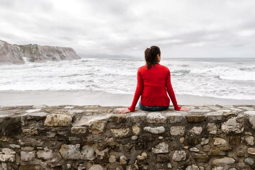 photo of woman resting on wall by ocean