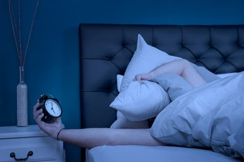 tired person holding alarm clock