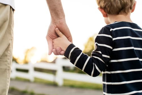 photo of father holding hands with young son