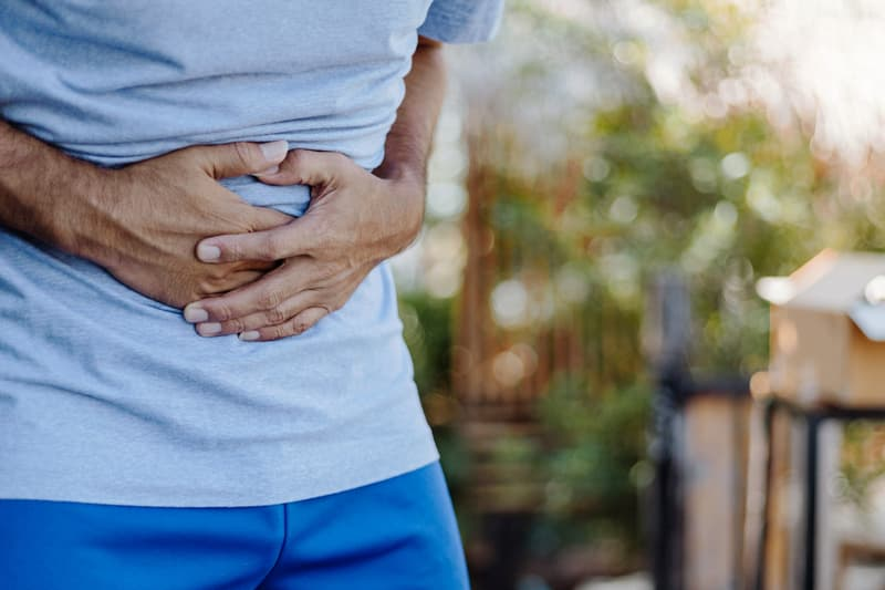 photo of man holding stomach