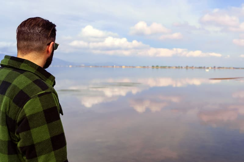 photo of man looking out over body of water