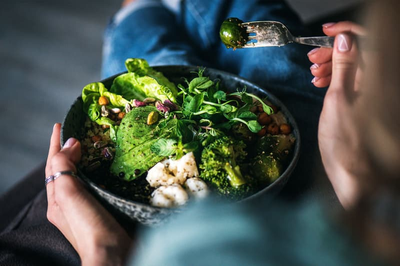 photo of woman eating vegetable bowl with hummus