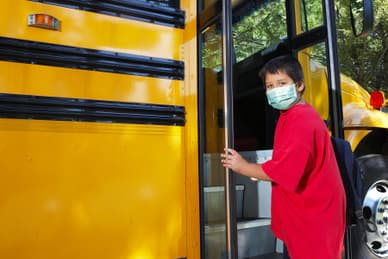 boy getting on school bus
