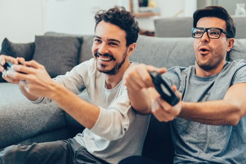 two guys playing video games at home