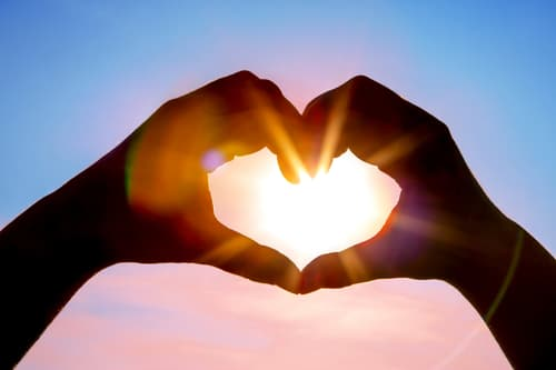 hands in shape of heart with sun