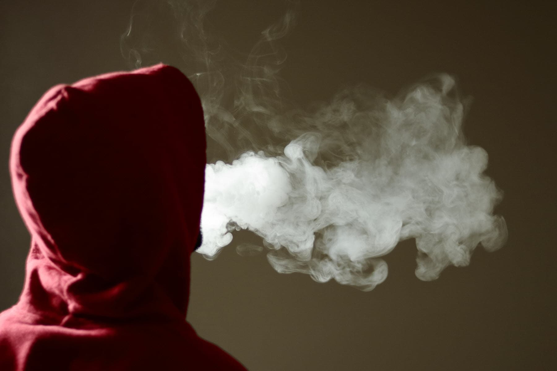 person in hoodie vaping