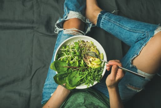 person eating bowl of vegetables