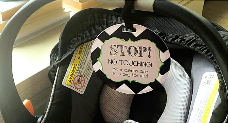 baby carry with sign that says do not touch