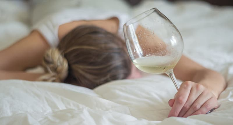 woman in bed with wine glass