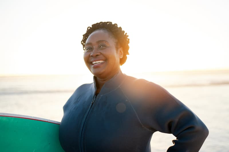 black woman with surfboard