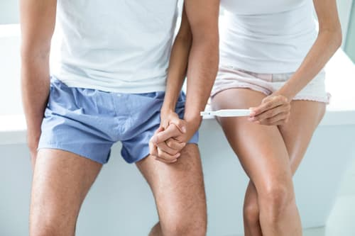 couple holding hands with pregnancy test
