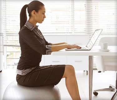 woman sitting on yoga ball at desk