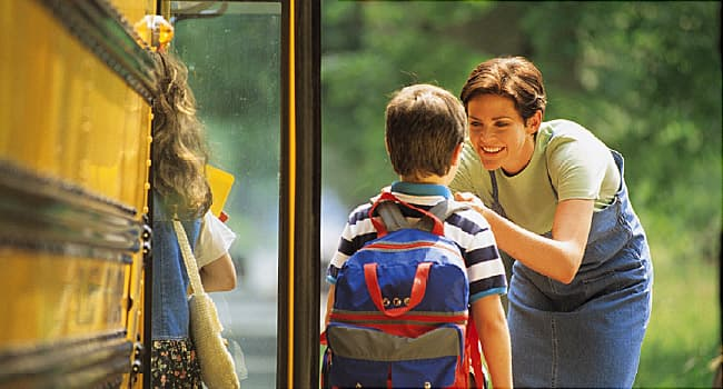Mother sending son off to school at bus stop
