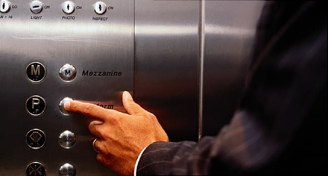 man pushing elevator button