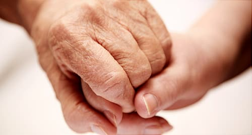 elderly parent holding hand of child