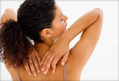 woman rubbing her upper back