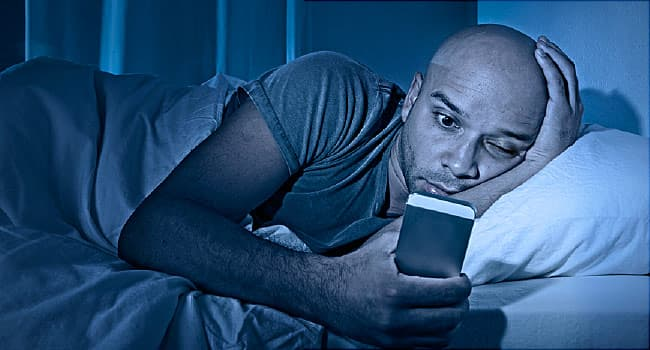 man using one eye at night to look at cell