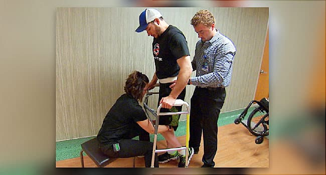 man learning to walk in physical therapy