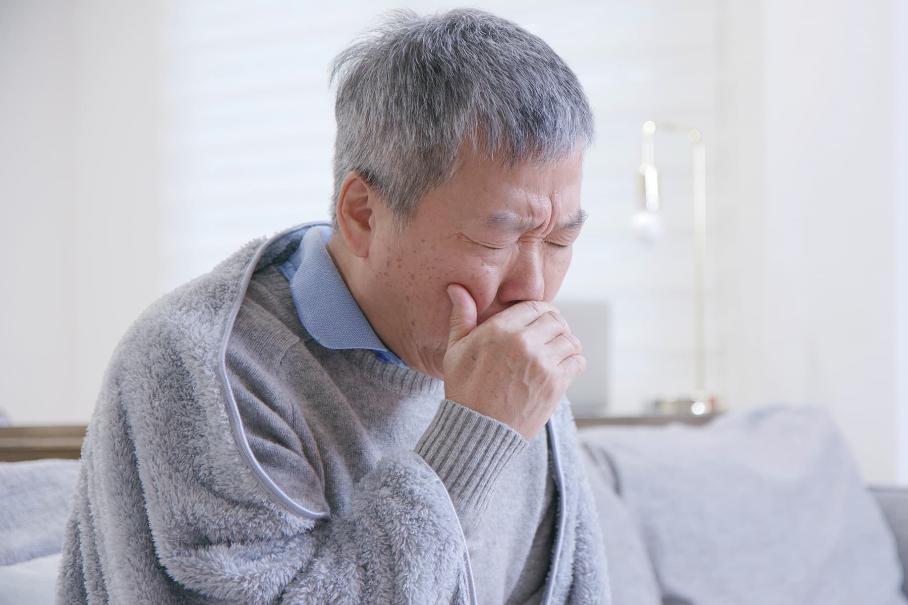photo of coughing senior man