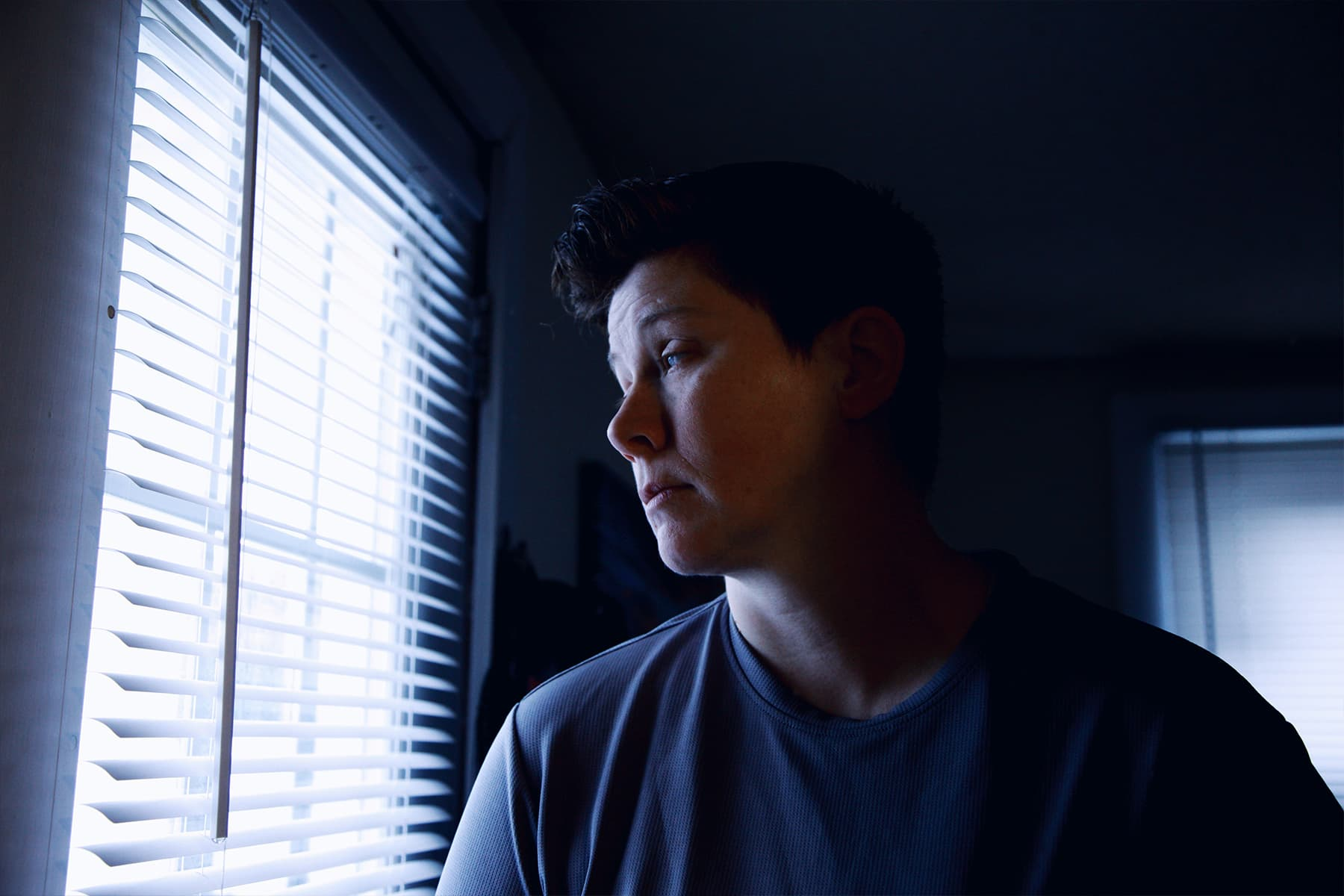 photo of woman peering out window