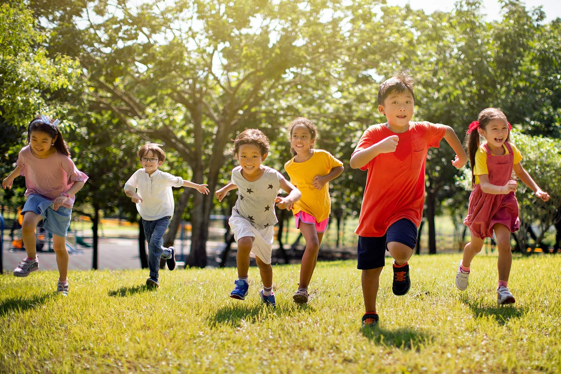 photo of young children laughing and running