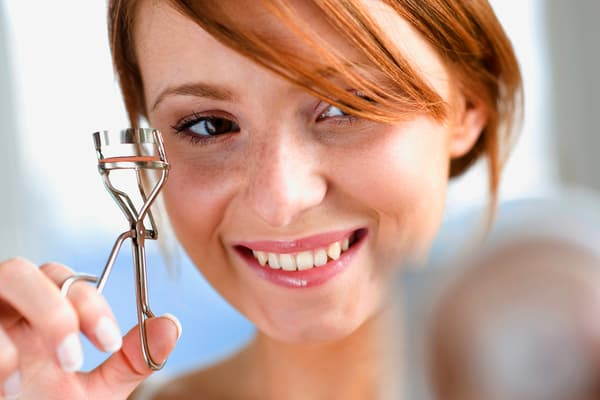 photo of woman using eyelash curlers
