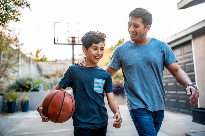 photo of father and son playing basketball