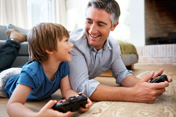 photo of father and son playing video games