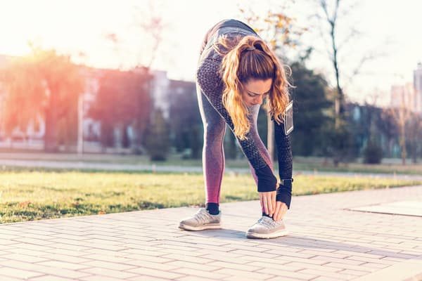 photo of fitness woman stretching legs outside