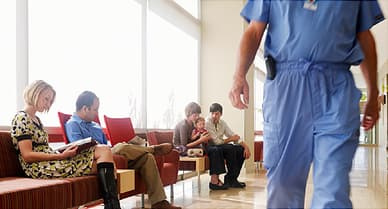 People in waiting area of hospital with surgeon