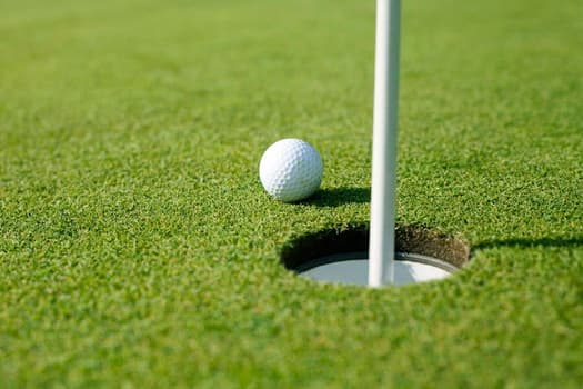photo of golf ball by hole close up