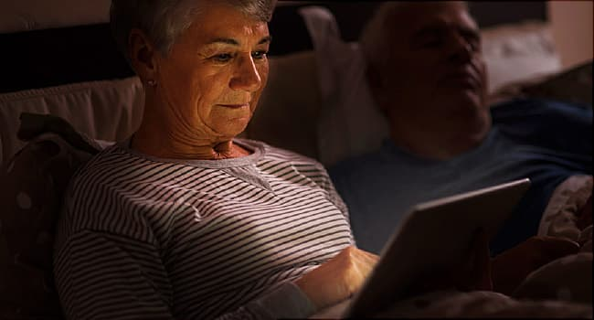 woman on tablet at night in bed