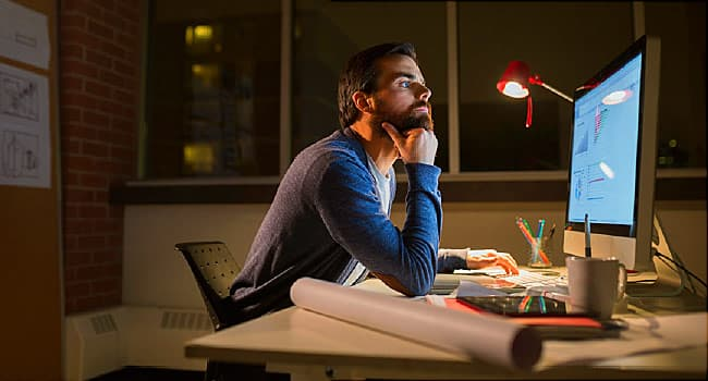 man working on computer at night