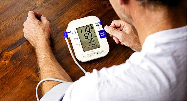 man checking blood pressure at home