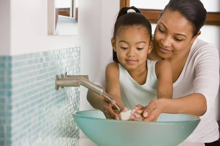 photo of mother washing daughters hands