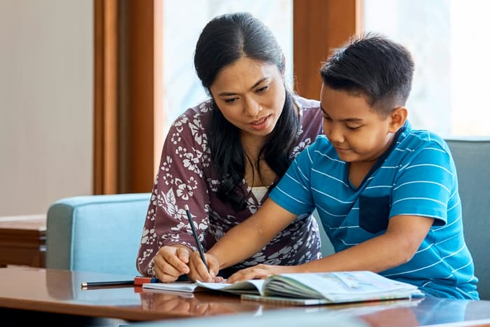 photo of mother helping son study at home