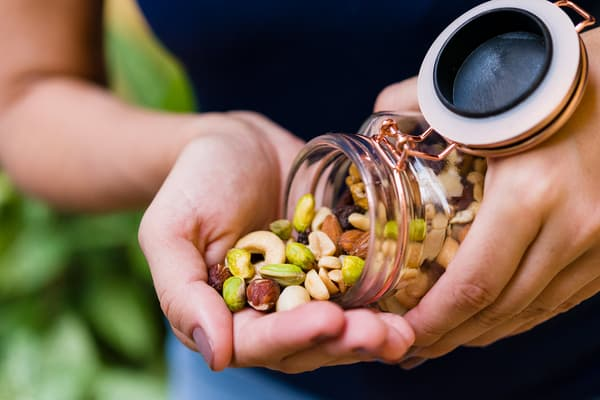 photo of woman pouring nuts into hand