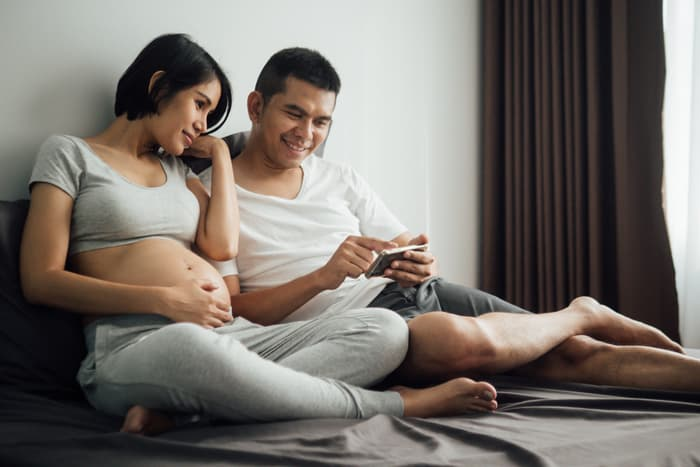 photo of pregnant couple watching smartphone video