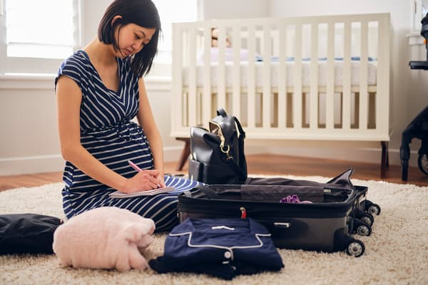 photo of pregnant woman packing suitcase