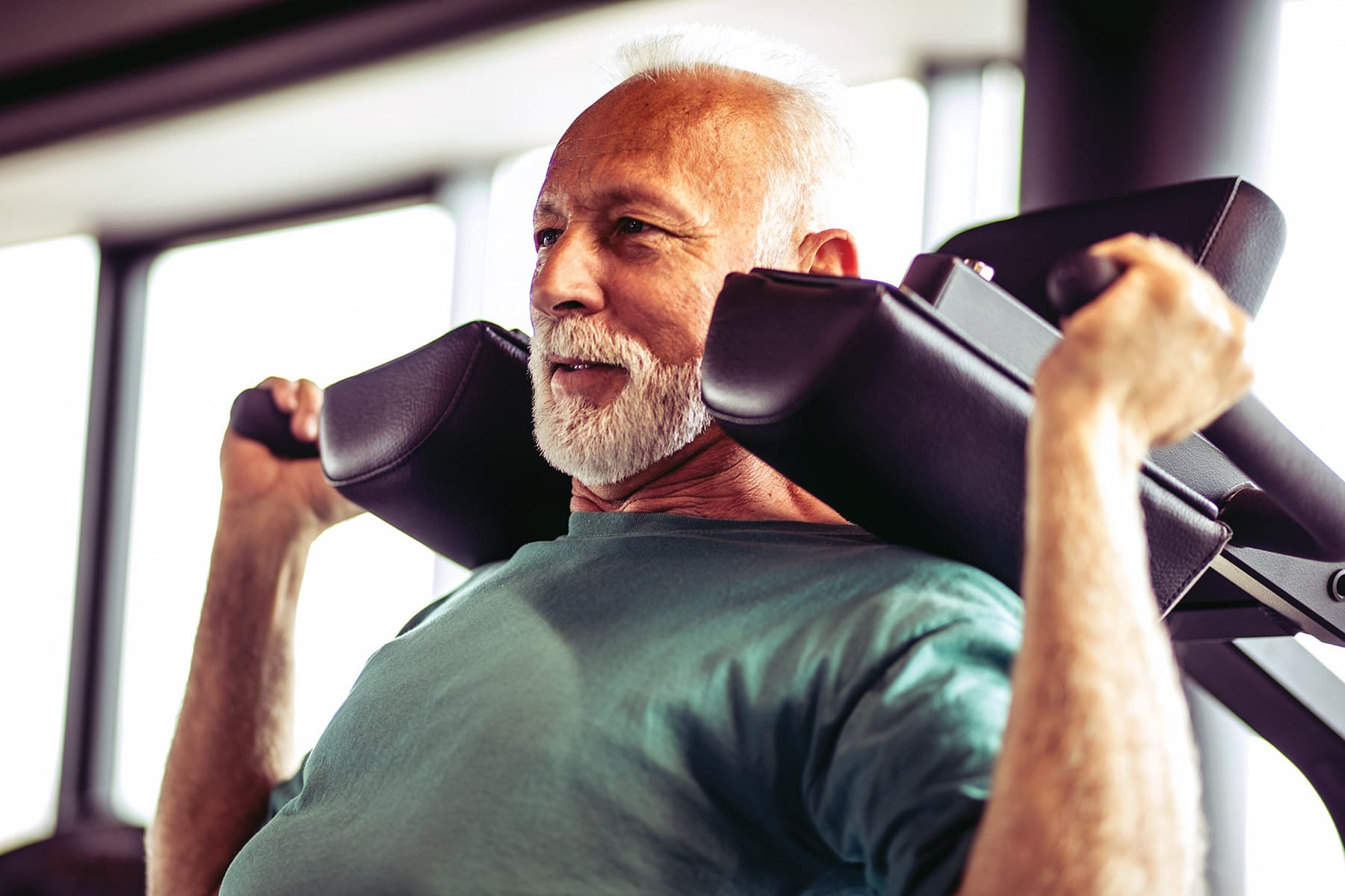 photo of senior man doing shoulder press in gym