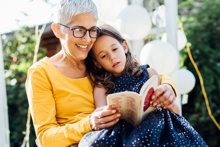 photo of senior woman reading to granddaughter
