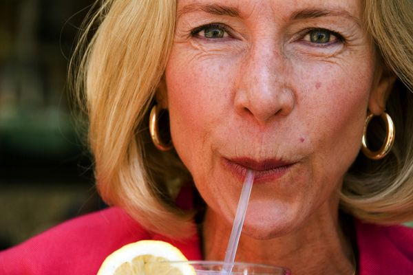 photo of woman drinking from straw
