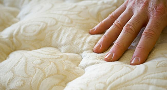 photo of hand pressing mattress