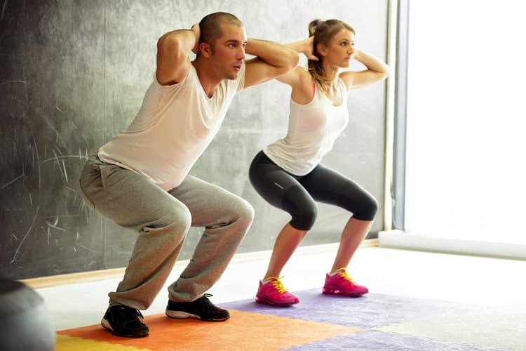 photo of man and woman doing squats