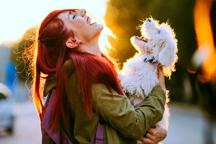 photo of woman and dog laughing