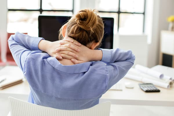 photo of woman at desk holding sore neck