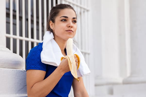 photo of woman eating a banana after workout