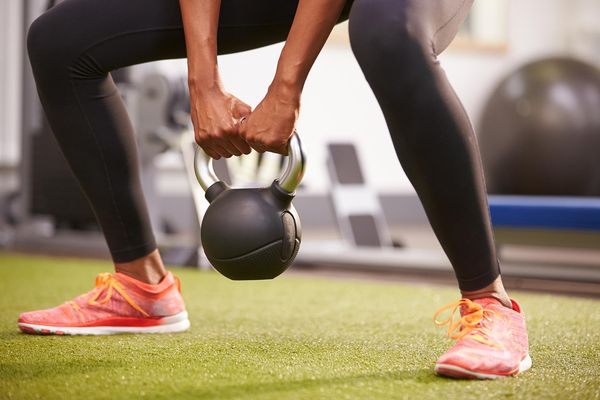 photo of woman exercising with kettlebell weight