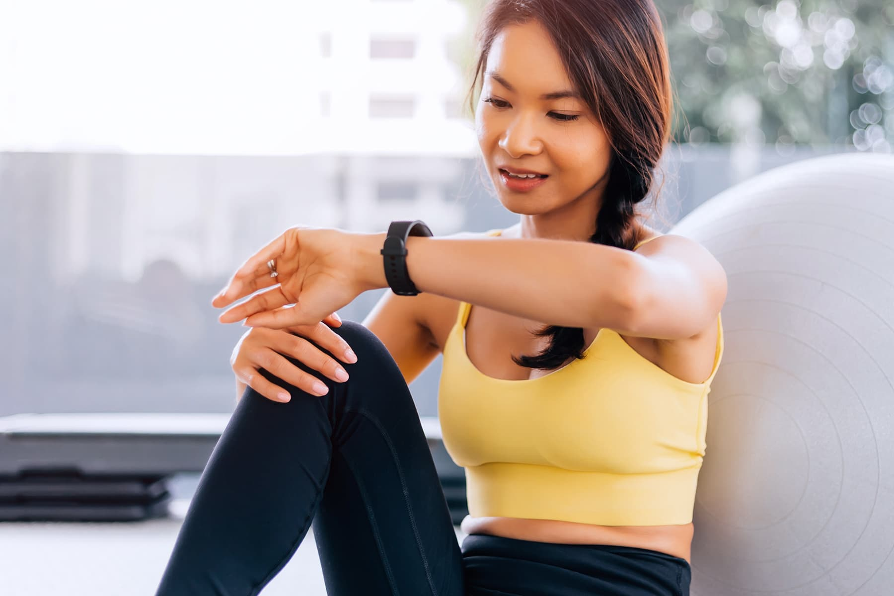 photo of woman in sports bra checking smartwatch
