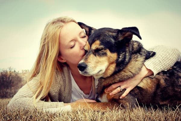 photo of woman kissing dog